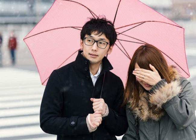 雨から女性を守る思わせぶりな男性